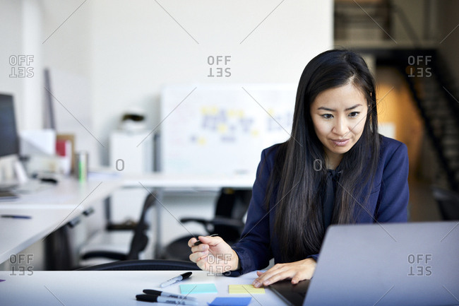 Confident businesswoman writing on adhesive notes while using laptop computer against wall in office
