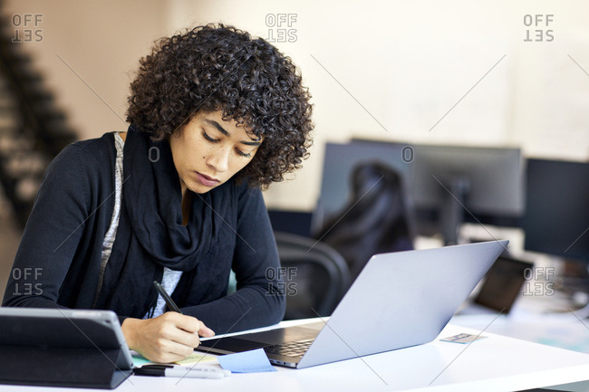 Confident businesswoman with curly hair writing on adhesive notes in office