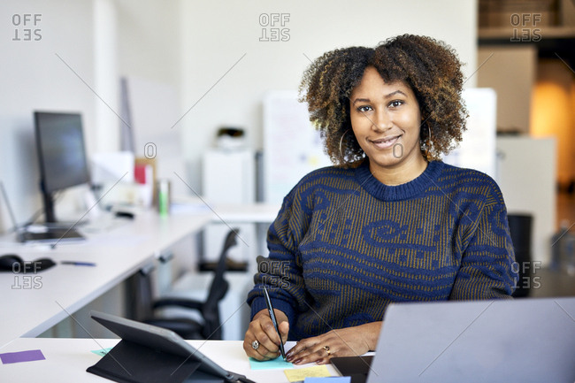Portrait of confident businesswoman with curly hair writing on adhesive notes in office