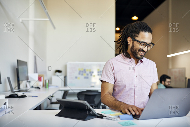 Smiling businessman with dreadlocks using laptop computer on desk in office