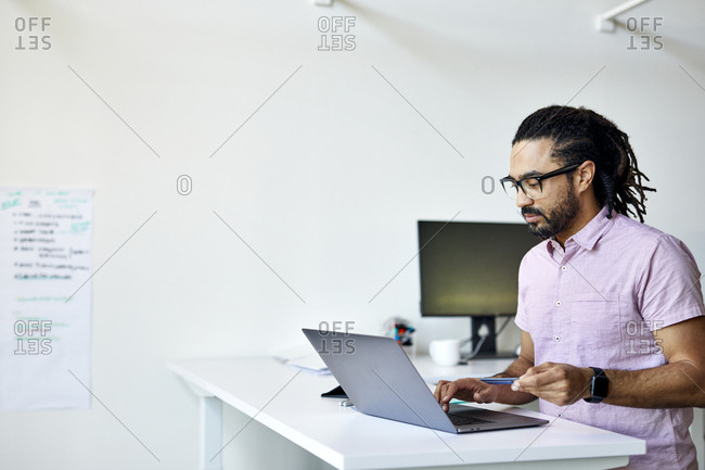 Businessman with credit card doing online shopping over laptop computer on desk in office