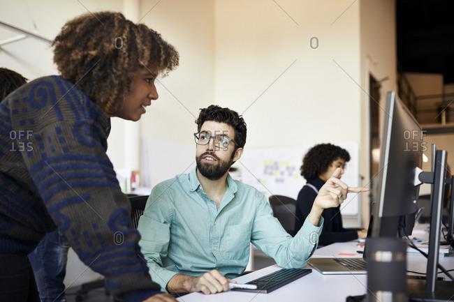 Businessman explaining to businesswoman over desktop computer at desk in office