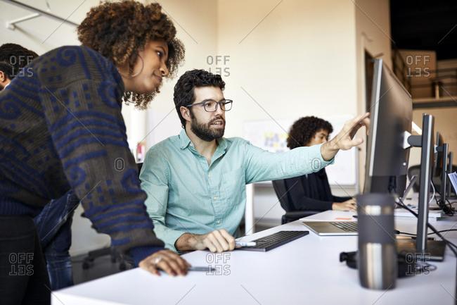Businessman explaining to businesswoman over desktop computer in office
