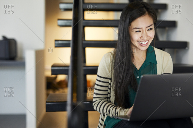 Smiling businesswoman using laptop computer while sitting on steps in office