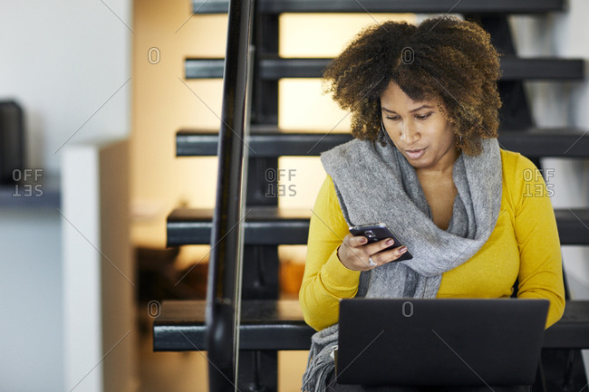 Businesswoman with laptop computer using mobile phone while sitting on steps in office