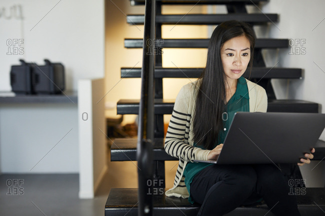 Confident businesswoman using laptop computer while sitting on steps in office