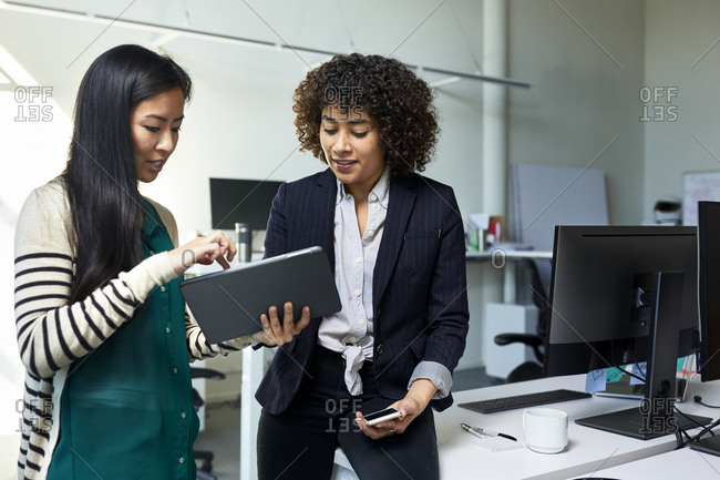 Businesswoman showing tablet computer to female colleague sitting on desk in office