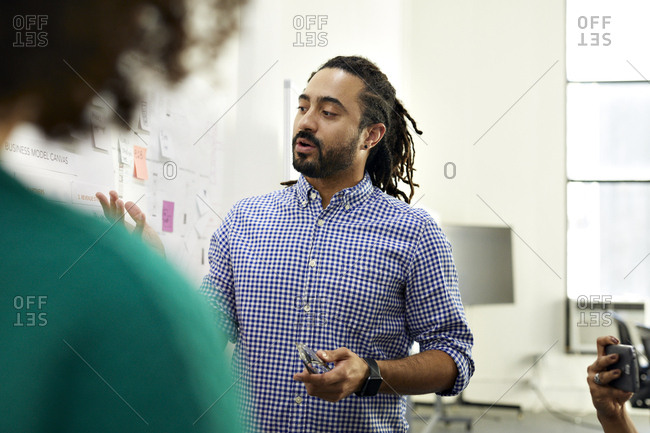 Businessman explaining business plan over whiteboard in meeting at office