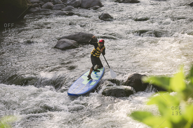 Young man on the SUP board at river