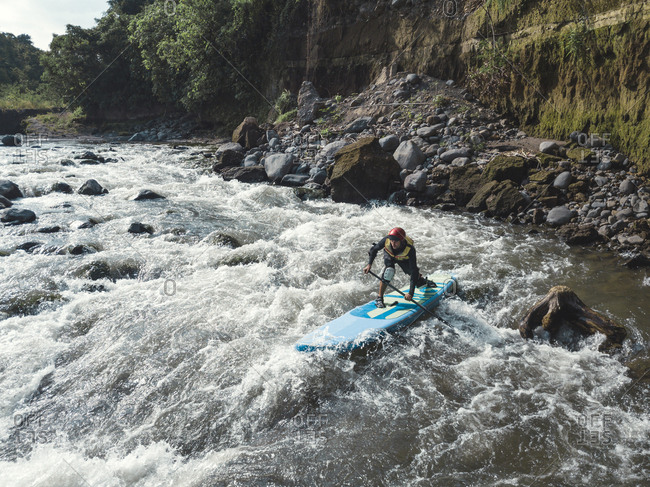 Man paddle boarding the river