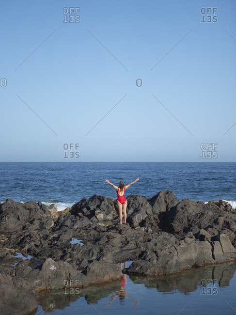 Rear view of carefree woman with arms outstretched on rocky coast