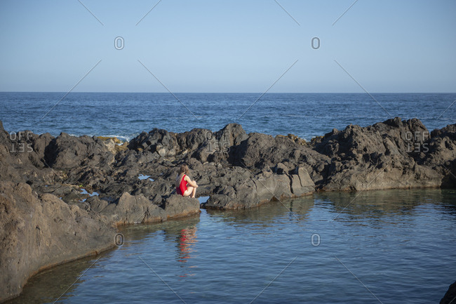 Woman in swimsuit sitting on rocky coastline and looking at the ocean