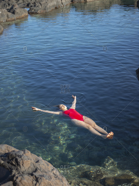 Young woman with arms outstretched floating in natural pool sunny day