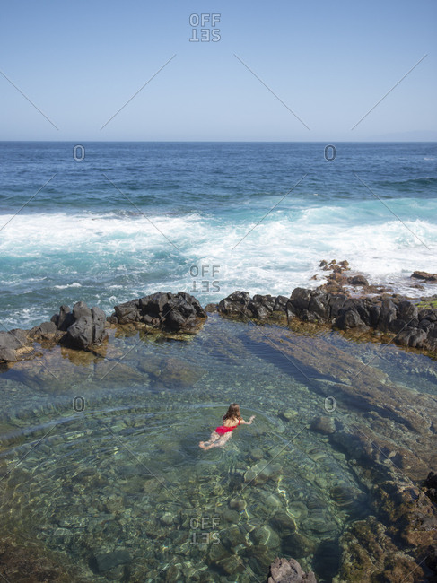 Woman swimming in natural pool against ocean and blue sky sunny day