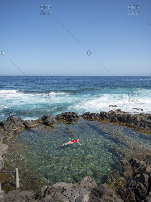 Woman with arms outstretched floating in natural pool against ocean