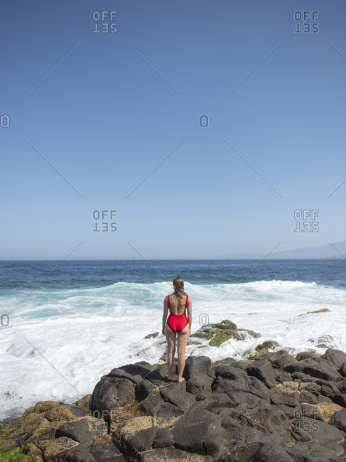 Rear view of woman standing on rocky coast and looking at ocean waves