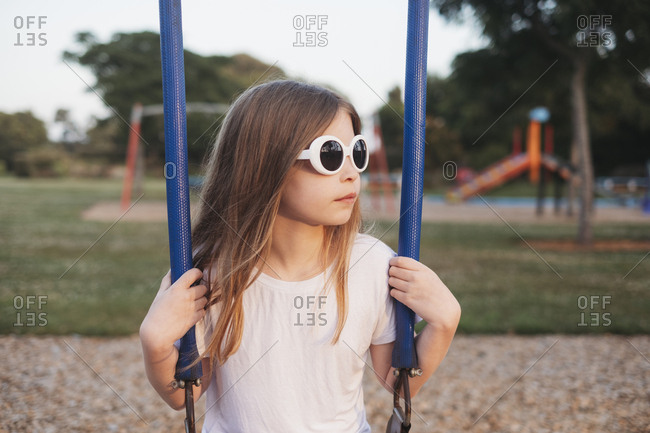 Young girl sitting on swing at playground during sunset