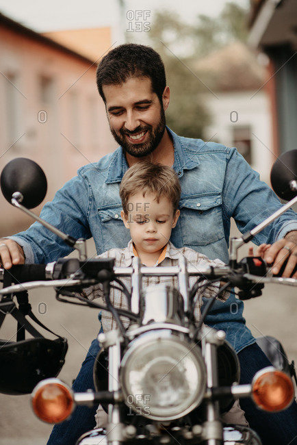 A happy father with his son drives a motorcycle