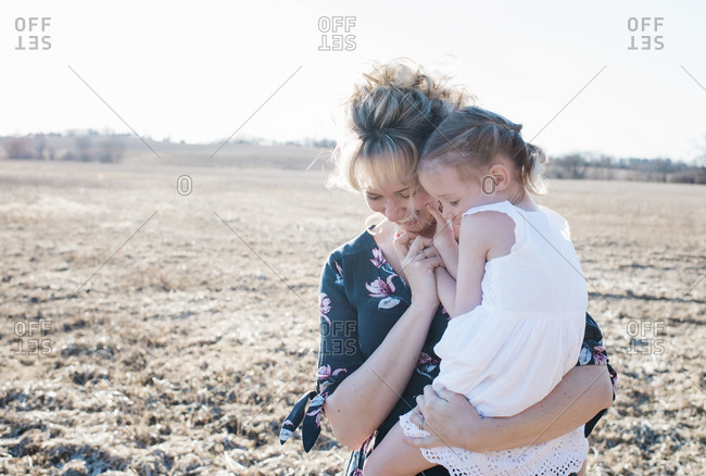 mother cuddling her daughter whilst laughing
