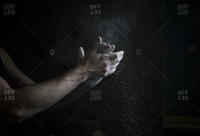 Man holding his hands together rubbing chalk for climbing