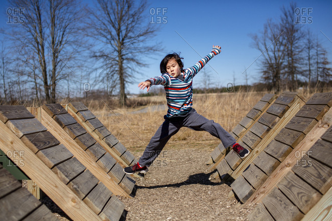 A focused child leaps across a series of wooden ramps in outdoor park