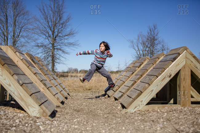 Portrait of a child mid-leap jumping across an obstacle course in park