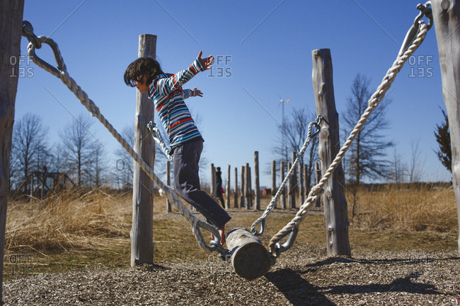 A barefoot child with arms outstretched leaps of a hanging log in park