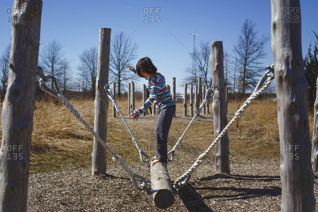 side view of a barefoot child balancing on a log in obstacle course