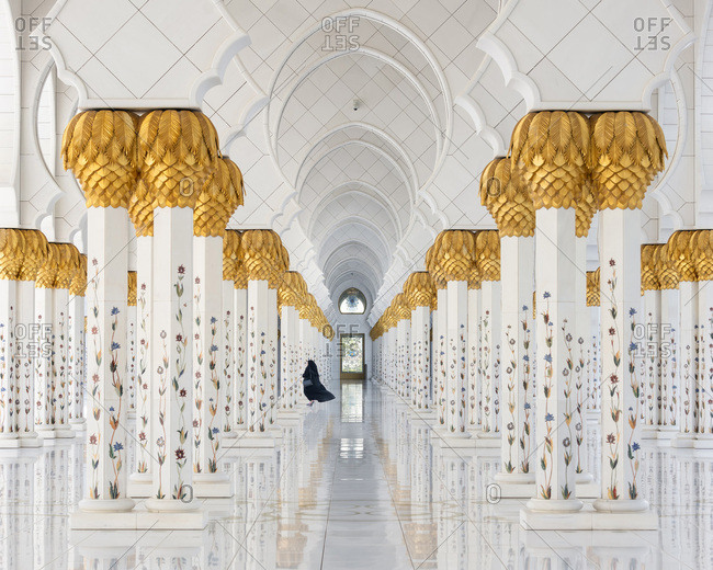 Sheikh Zayed Grand Mosque, Abu Dhabi, United Arab Emirates - March 16, 2019: Woman in black robe between Architectural columns, Sheikh Zayed Mosque
