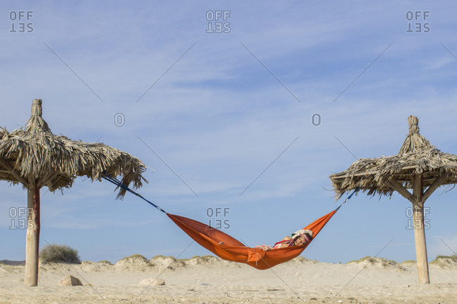 Woman on vacation taking a nap in a hammock at the beach