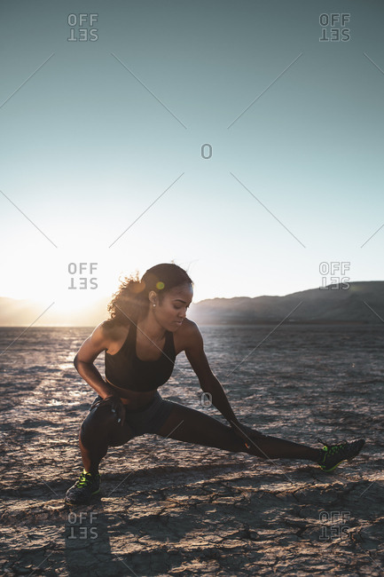 Full length of woman stretching at desert during sunset