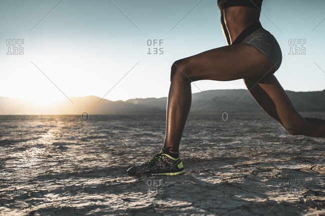 Low section of woman practicing lunges at desert during sunset