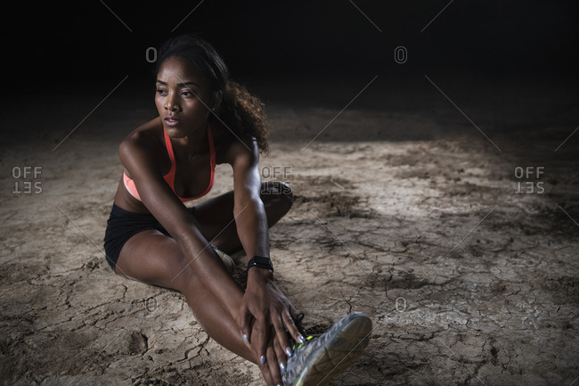 Full length of young woman stretching in Mojave desert at night