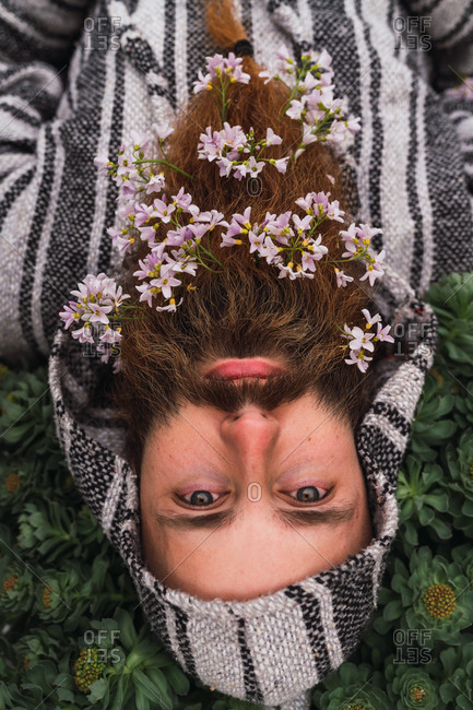 From above handsome bearded man in striped hooded sweater lying in green grass with flowers in lush beautiful beard