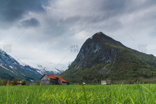 Gray cloudy sky over snowy mountain ridge and small settlement in green valley in Norway