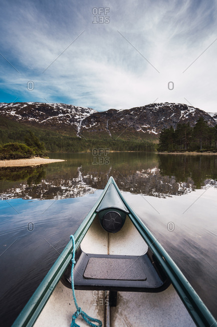 Shabby boat floating on tranquil surface of clean lake towards snowy mountain range on cloudy day in Norway