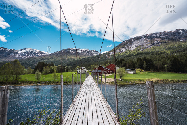 Narrow wooden bridge crossing calm river and leading to small settlement near mountains on cloudy day in Norway