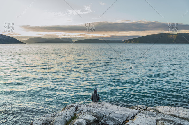 Back view of tourist sitting on rocky shore near rippling sea and admiring sundown in cloudy evening in Norway