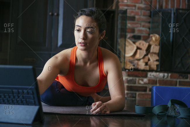 Mid adult woman learning stretching from laptop in room
