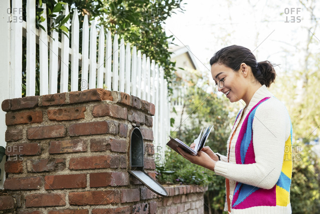 Side view of smiling beautiful woman reading mail
