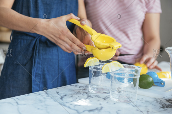 Midsection of women making fresh lemonade juice in kitchen at home