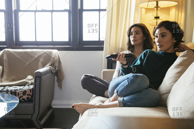 Young woman holding remote control while sitting with sister on sofa