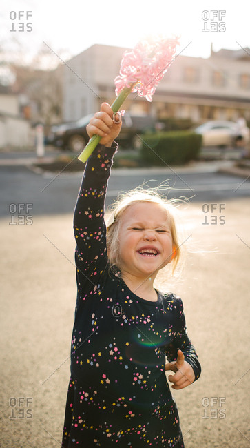 Young girl holding pink flowers up in the air