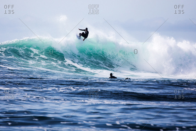 Surfers riding a large cresting wave