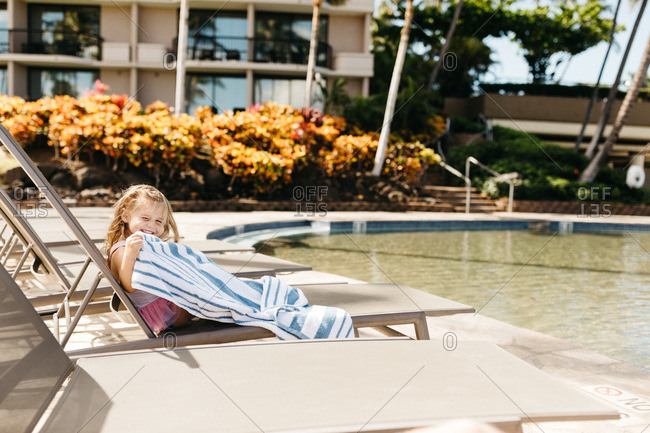 Happy blonde girl sitting poolside at hotel