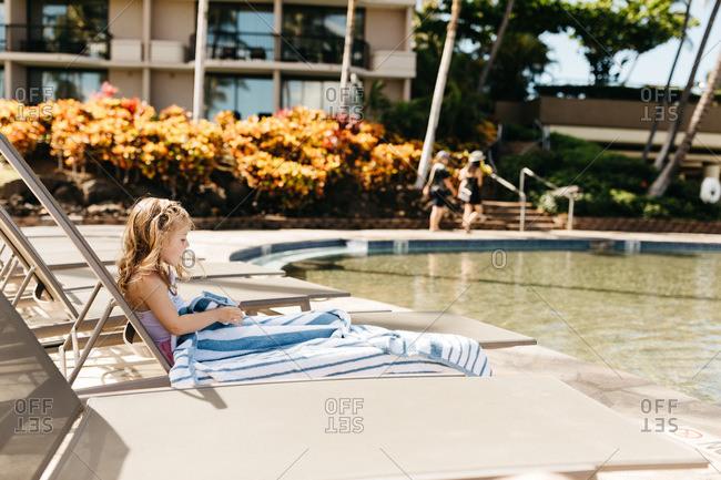Little blonde girl sitting poolside at hotel