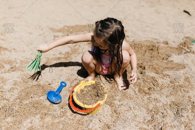 Little girl playing in the sand with bucket and toys