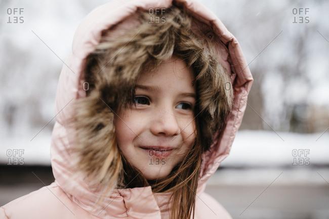 Portrait of a little girl wearing warm coat outdoors in winter
