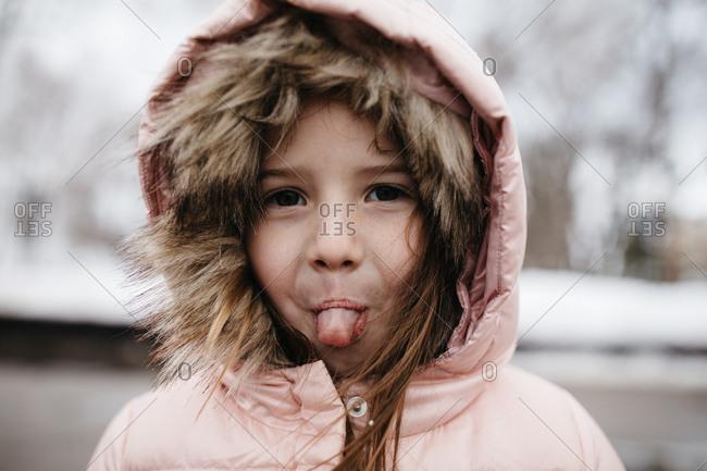 Little girl wearing warm coat outdoors in winter