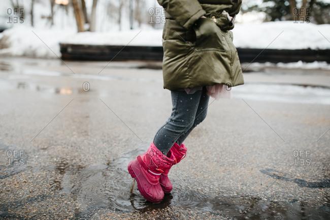Little girl splashing in melting snow puddles in the street